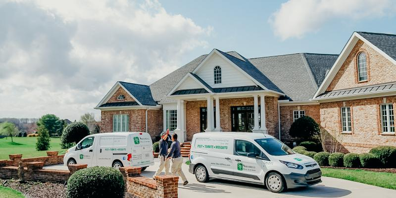 technicians outside of a home next to Sherrill Pest Control vans